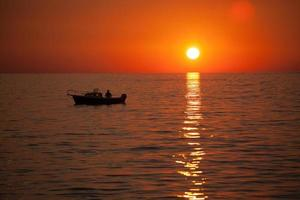 pescador en un barco durante la puesta de sol foto