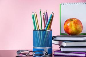 volver al concepto de escuela. útiles escolares, libros y manzana sobre fondo rosa. lugar para el texto. foto