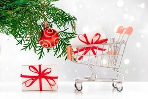 New Year shopping. Mini cart with gift boxes on white background. photo