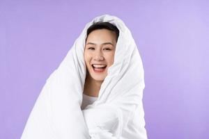 Asian woman curled up in blanket on purple background photo