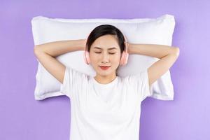 Mujer asiática sosteniendo la almohada superior, aislado sobre fondo púrpura foto