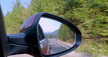 Cerca del espejo retrovisor del coche con carreteras montañas y bosques video