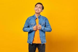 Smiling Asian man wearing blue jacket looking at empty space with hope on yellow background photo