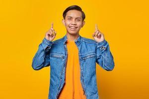 Retrato de alegre joven asiático apuntando a la promoción de publicidad en vivo aislado sobre fondo amarillo foto