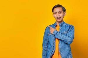 Portrait of a cheerful and excited Asian man pointing to an empty space isolated on yellow background photo