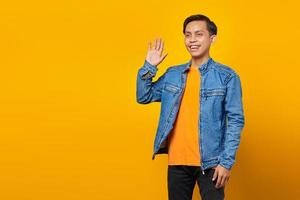 Portrait of smiling Asian young man greeting empty space on yellow background photo
