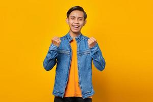 Portrait of excited young Asian man celebrating success with raised hands isolated on yellow background photo