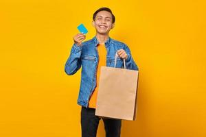 Portrait of cheerful asian man holding shopping bag and showing credit card over yellow background photo