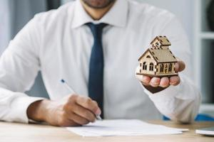 writing real estate agent holding house photo