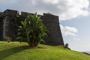 The Sao Joao Baptista fortres with a green lawn in foreground and a cloudy sky in backgrounda photo