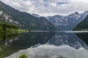 Hallstatter sea with reflections of the alps and the sky in the calm water. photo