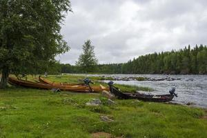 Boats used for fishing in the rapids with rapid and a cloudy sky in background photo