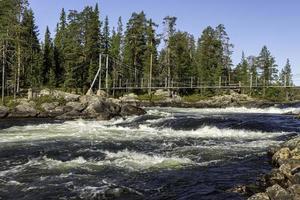 Parte del puente colgante sobre el rápido Trollforsen en Pite River en el norte de Suecia foto