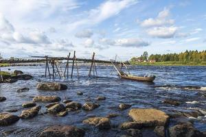 Bridge in kukkola rapid with a fishermans boat attached. photo