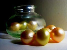 Colorful shinning beads alongside a jar photo