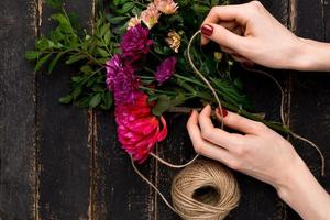 Bouquet of flowers in female hand on a black wooden table photo