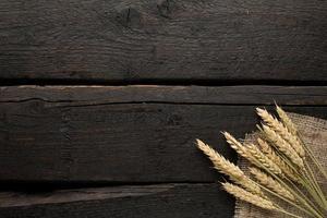 Espiguillas de trigo sobre arpillera sobre fondo de madera foto