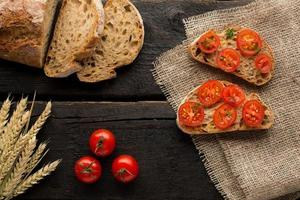 Toasts with tomatoes and bread on a board on a wooden background photo
