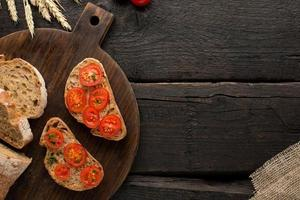 Wooden background with tomatoes toasts and bread on a board photo