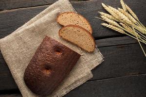 pan fresco con trigo sobre un fondo de madera foto