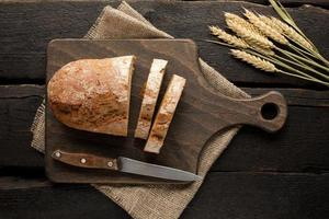 Fresh bread on a board with wheat on a wooden background photo