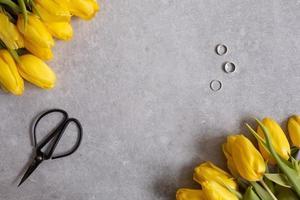 Fondo gris con flores amarillas tulipanes y tijeras vista superior foto