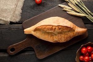 Pan fresco en una tabla con trigo sobre un fondo de madera foto