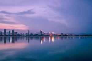 At dusk, the lake reflects the night view of the city photo