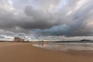 The sky is covered with dark clouds and the beach is cloudy photo