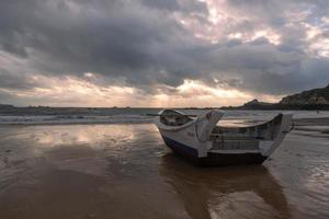 A small boat docked on the cloudy beach, and the sky was covered with dark clouds photo