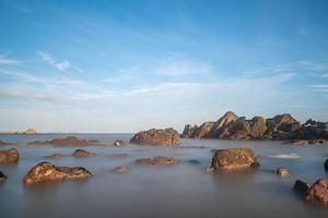 Sea water and reefs by the sea under the blue sky photo