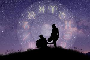Astrological zodiac signs inside of horoscope circle. Couple singing and dancing over the zodiac wheel. photo