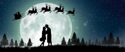 silueta de santa claus en la noche de navidad con pareja bailando bajo la luna llena. foto