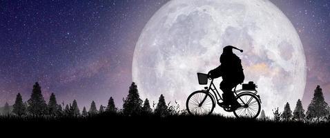 silueta de santa claus montando en su bicicleta sobre la luna llena. foto