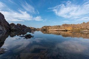 agua de mar y arrecifes junto al mar bajo el cielo azul foto