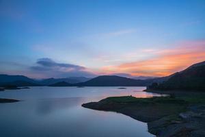 el lago de la tarde reflejaba las montañas y el cielo a ambos lados foto