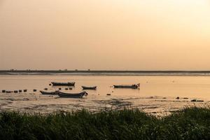 al amanecer por la mañana, el agua del mar refleja el barco de pesca foto