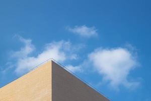 parte del edificio amarillo claro bajo el cielo azul y nubes blancas foto