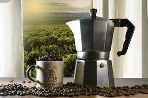 Granos de café en una taza y cafetera italiana sobre una mesa de madera con campo de café visto a través de una ventana en Brasil foto