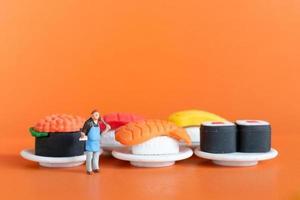 Tiny Chef making Sushi set on orange background photo