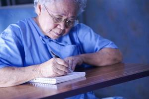 Asian senior or elderly old lady woman patient writing while sitting on bed in nursing hospital ward, healthy strong medical concept photo