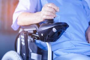 Asian senior or elderly old lady woman patient on electric wheelchair with remote control at nursing hospital ward, healthy strong medical concept photo
