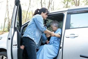 Help and support asian senior or elderly old lady woman patient get to her car, healthy strong medical concept. photo