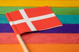 Denmark flag on rainbow background flag symbol of LGBT gay pride month  social movement rainbow flag is a symbol of lesbian, gay, bisexual, transgender, human rights, tolerance and peace. photo