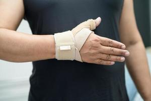 Asian middle-aged lady woman use elastic bandage to treating De Quervain syndrome at hand and finger in office. photo