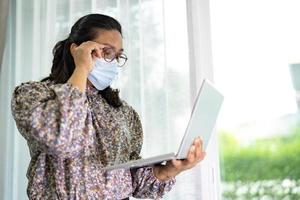 mujer de negocios asiática trabajar desde casa comunicarse con la oficina por videollamada de conferencia en la computadora portátil, quedarse en casa. foto