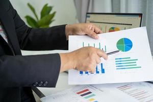 Asian accountant working and analyzing financial reports project accounting with chart graph in modern office, finance and business concept. photo