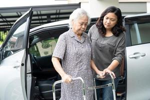 Help and support asian senior or elderly old lady woman patient walk with walker prepare get to her car, healthy strong medical concept. photo