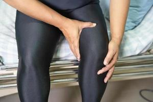 Asian middle-aged lady woman patient touch and feel pain her knee, healthy medical concept. photo
