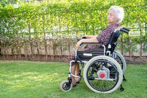 Paciente asiático mayor o anciano en silla de ruedas eléctrica con control remoto en la sala del hospital de enfermería, concepto médico fuerte y saludable foto
